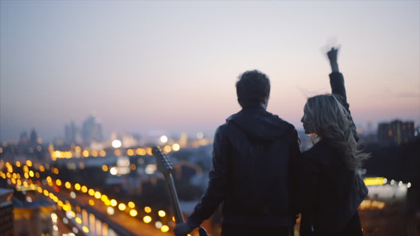 couple in rock-n-roll style standing on the roof with guitar in hand expression makes the rock n roll gesture in evening time at blured city lights background slow motion shot .