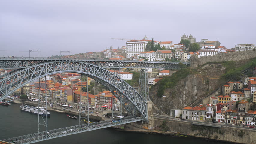 Beautiful timelapse with cars and people moving by the steel bridge Ponte Dom Luis I over the river Douro in Oporto, Portugal.