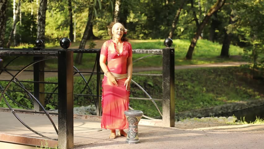 Beautiful woman in red dress dance bellydance near darbuka on bridge in park at sunny day.