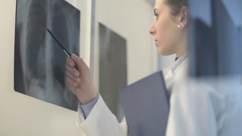 Doctors working together in the office and examining a patient's x-ray: healthcare, diagnosis and medicine concept