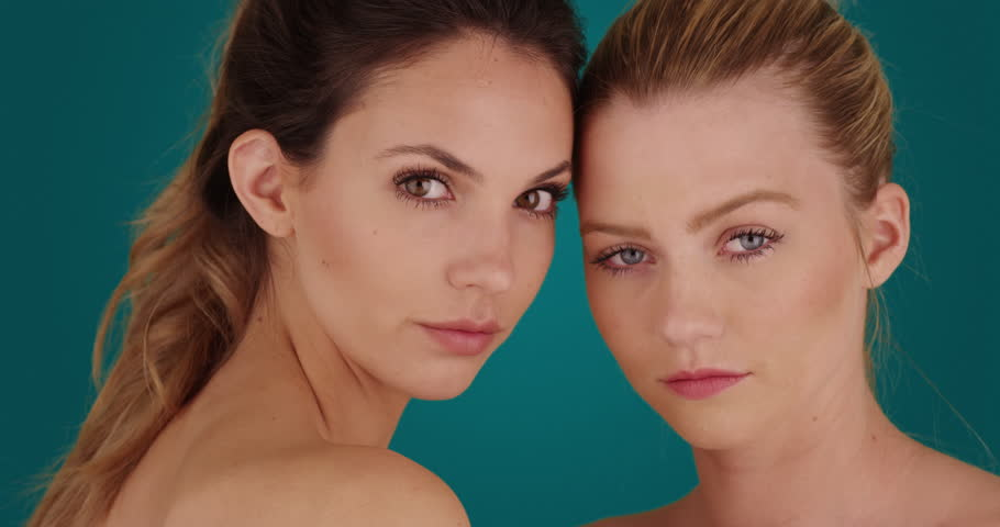 Pair of gorgeous females wearing makeup posing with seriousness on solid blue background. Two somber-looking women with make-up on staring at camera on blue background. 4k