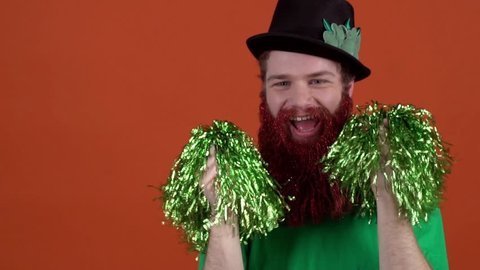 Young man celebrating saint patrick's day isolated on orange dancing with pom poms