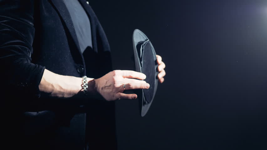 Magician is straightening his hat and twisting it in his hands.
