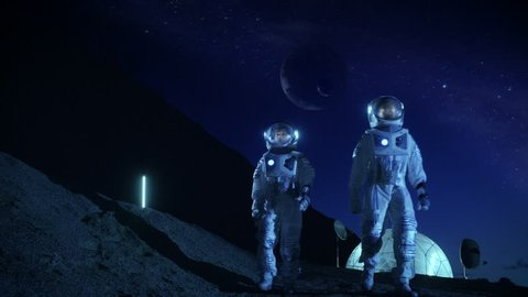 Two Astronauts in Space Suits Exploring Newly Discovered Planet. In the Background Space Base with Habitable Dome, in the Sky Outer Planets are seen. Futuristic Concept on Space Colonization.