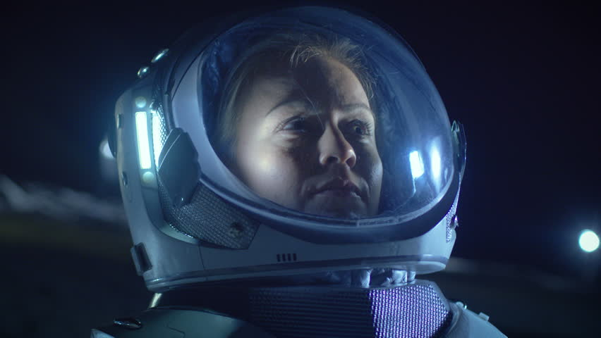 Portrait of the Beautiful Female Astronaut on the Alien Planet Looking around in Wonder. In the Background Living Quarters. Space Travel, Exploration and Solar System Colonization Concept.
