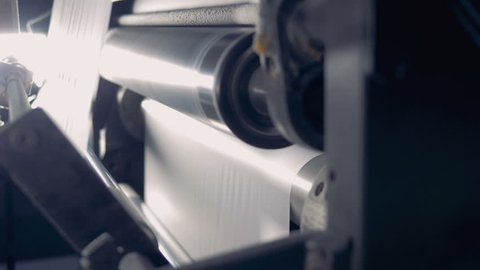 Close up of a paper rolling on a production line. Paper recycling factory equipment.