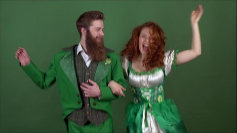 Young couple in costumes celebrating saint patrick's day isolated on green wall dancing together