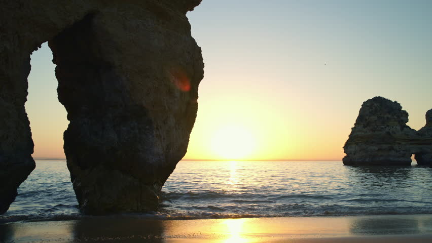 Beautiful sunrise on the rocky atlantic ocean coast with in Lagos, Portugal. Popular summer travel destination and famous beach with coastal cliffs - Ponta da Piedade