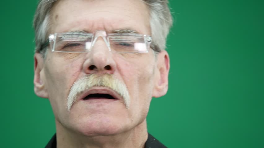Senior man wearing glasses isolated on green background | Shutterstock HD Video #1007775796