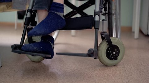 Close-up, low angle shot disabled young guy with spinal cord and leg problems (multiple sclerosis) puts feet on wheelchair footrest