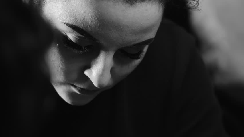 Young beautiful womans face, she makes tattoo. Close up working with machine. Slow motion. Black and white footage #1007808526
