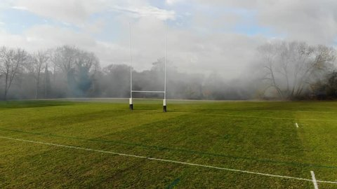 Drone Shot Of Rugby Pitch With Smoke Blowing Across, English Countryside, Cloudy Blue Sky