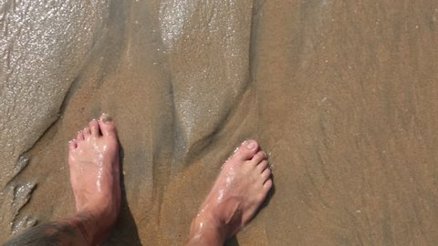 Man's feet washed by ocean waves and buries them in the sand. Point of view of young man stepping at the golden sand at sea beach. Bare foot of guy going on sandy shore with