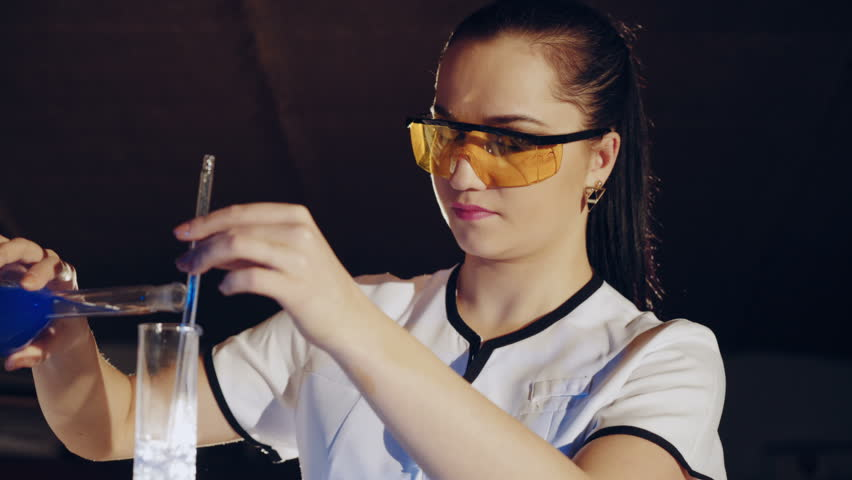 Woman scientist mixing together two liquid substances. Laboratory examination. | Shutterstock HD Video #1007873746