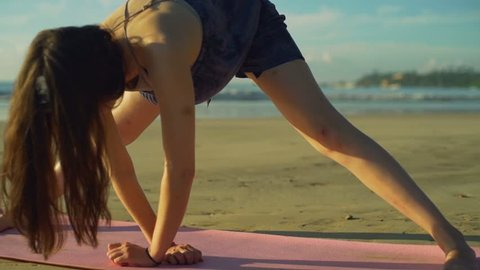 Group of women do yoga leg stretch pose on beach sunrise rapid slow motion