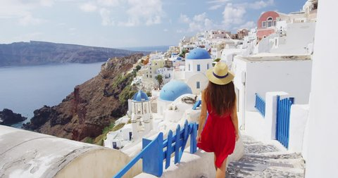 Vacation -Tourist travel woman in Oia, Santorini, Greece. Happy young woman walking on stairs by famous blue dome church landmark destination. Beautiful girl in red dress on visiting the Greek island.