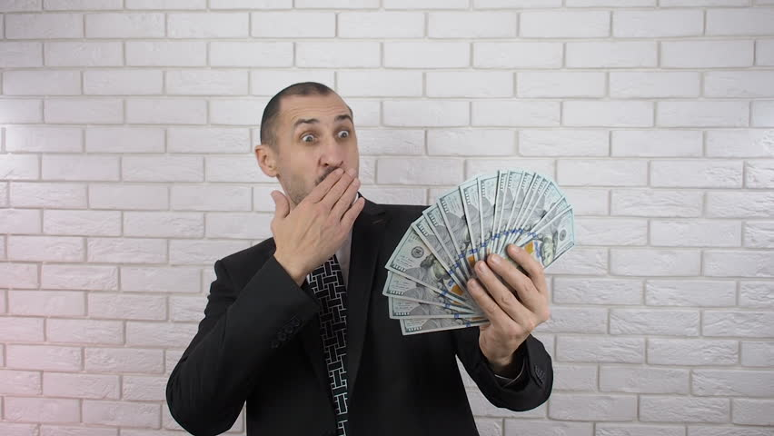Gesture of surprise. A business man is surprised by money.