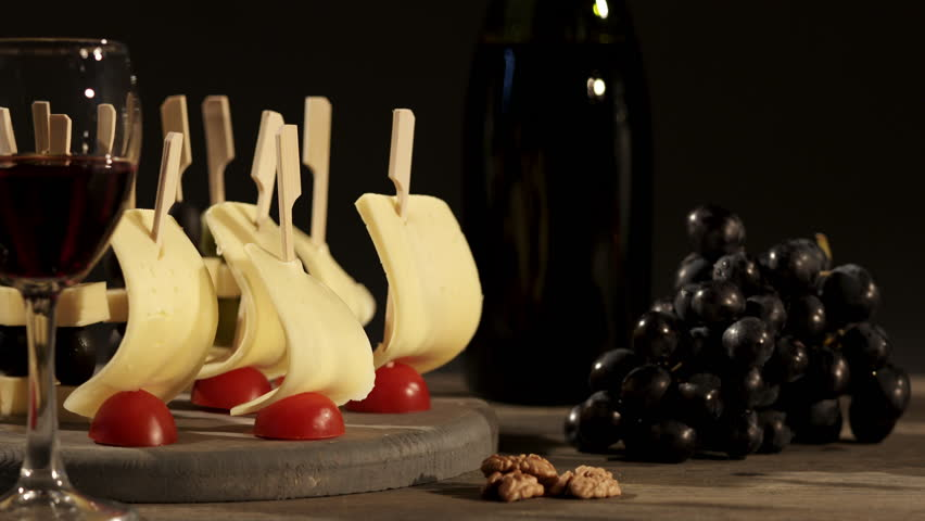 Cheese and wine tasting. Two glasses with red wine, grapes and cheese skewers on wooden tray. Close-up of cheese appetizers with cherry tomatoes and olives on a dark background. Dolly shot