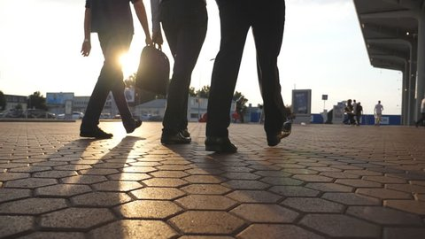 Feet of three businessmen walking near airport with sun flare at background. Business men go to terminal together. Confident guys being on his way to work trip. Colleagues going outdoor. Slow motion