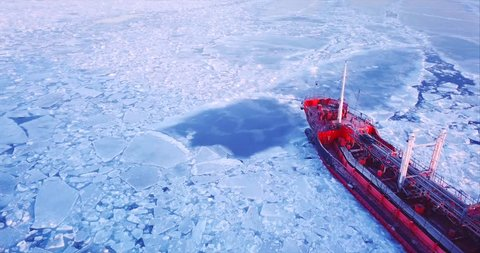Close aerial view of the ship slowly moving through ice floes. Flying above the Eastern Bosphorus strait. Vladivostok, Russia. Evening