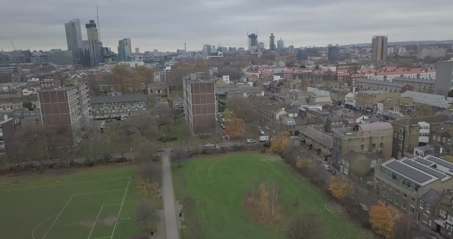 Cinematic Aerial Shot Flying Towards London's The City from East London Bethnal Green Road Over Parks, Houses and Flats