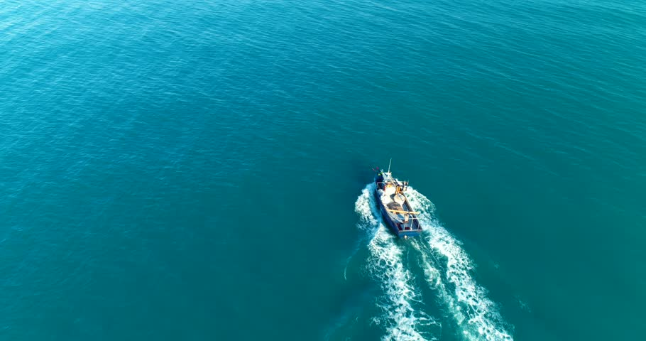 120 Aerial 4k cinematic  ,  fishing boat with fishermen preparing the  fishing nets for work