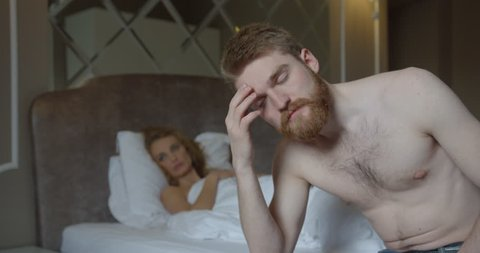 Close-up portrait of the depressed ginger head man sitting on the bed at the blurred background of his blonde wife lying on it.