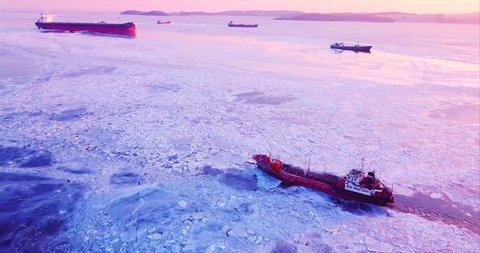 Flying above the Eastern Bosphorus strait. Aerial view of the ship slowly moving through ice floes. Others are stuck on the background. Vladivostok, Russia. Evening