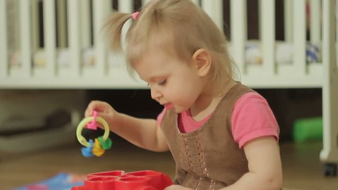 Little girl is playing with plastic toys at home or in kindergarten, baby child intellectual games of children