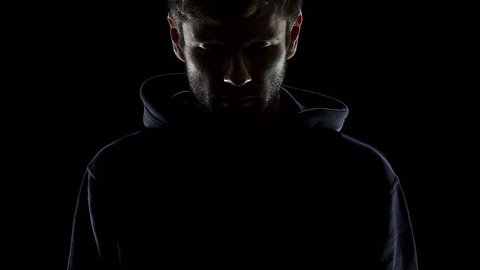 Bearded man putting on hood, hiding from people, anonymous dark silhouette