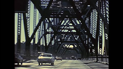 POV of vintage car crossing Oakland Bay Bridge passing by Treasure Island to Oakland. Archival footage in eighties. San Francisco, California, United States in 1980.