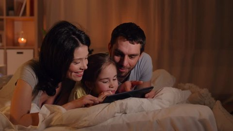 people and family concept - happy mother, father and little daughter with tablet pc computer in bed at night at home