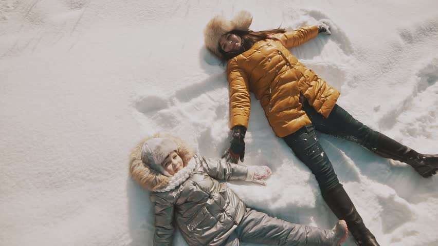 Young mother and little daughter making angels on the snow. Top view with copyspace. Family have fun in sunny winter day outdoors | Shutterstock HD Video #1008042346