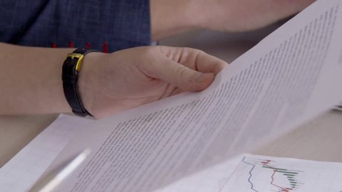 Close-up of person is study important document with text with pen in hands. Specialist reads on paper an analytical note to schedule of stock quotes, bitcoin, and crypto currency in foreign exchange