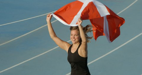 A Danish Athlete celebrating with the national Flag of Denmark.