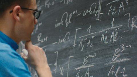 Brilliant Young Mathematician Writes Complex Math Equation/ Formula on the Blackboard. Shot on RED EPIC-W 8K Helium Cinema Camera.