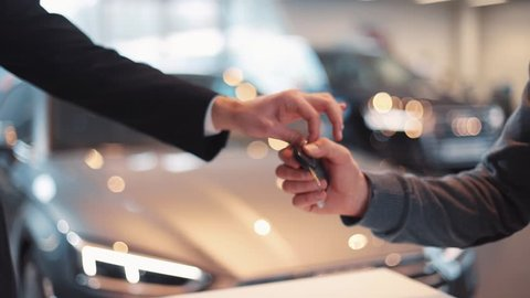 Seller of machines giving keys to buyer. Men shaking hands each other in car dealership, making purchase deal on background of beautiful car.