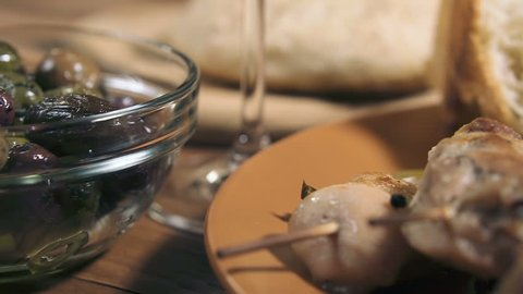 Panning shot of grilled chicken meat, bowl with different kind of olives, glass of wine, cheese and fresh bread ciabatta on the wooden table, close-up.