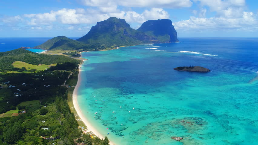 Aerial view of Lord Howe Island (World Heritage-listed paradise), turquoise blue lagoon and Mount Gower on background - New South Wales - Tasman Sea - Australia from above, 4k UHD #1008115336
