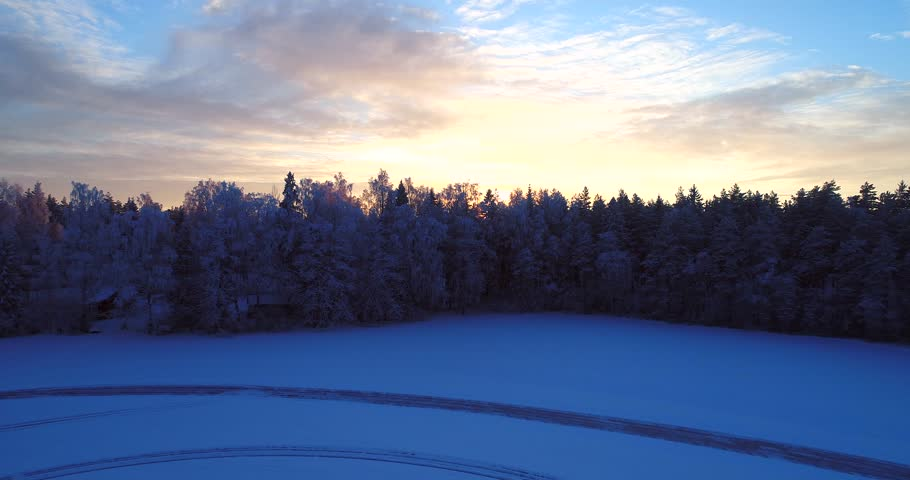 Sunset winter landscape, Cinema 4k aerial view over a frozen trees, revealing a snowy nature and train tracks, in a frosty forest, on a sunny winter evening dawn, in Uusimaa, Finland