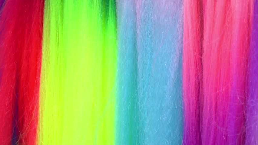 Red,  blue,  yellow,  green and pink artificial hair are waving in the summer wind.  #1008144796