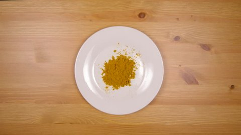 Female hand reaches in and removes plate of curry powder from wood table in 4k top down view with wooden table background.