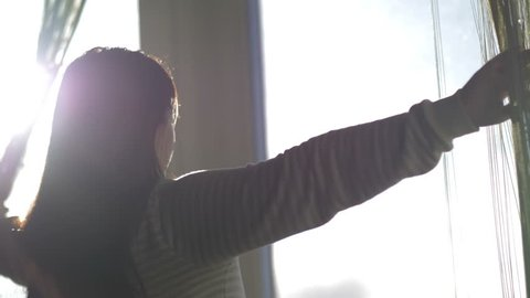 woman opening window curtains at home, back view. Good morning, new day, sun rays