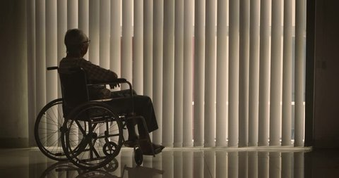 Silhouette of lonely old man sitting on wheelchair while looking at the window with curtain at home. Shot in 4k resolution