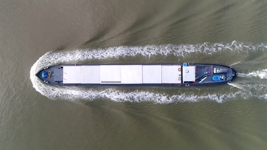 Aerial top down footage of barge moving over canal this flat-bottomed boat is mainly built for river and canal transport of heavy goods most barges are self-propelled steady footage 4k resolution