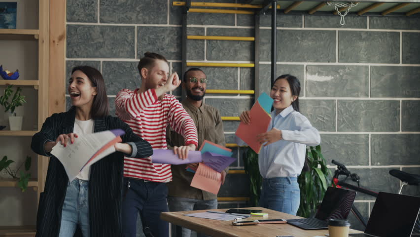 Diverse group female and male start-up business team have fun dancing party in modern office throwing paper documents and celebrating success of project | Shutterstock HD Video #1008210976