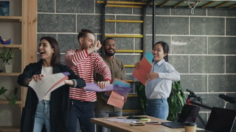 Diverse group female and male start-up business team have fun dancing party in modern office throwing paper documents and celebrating success of project
