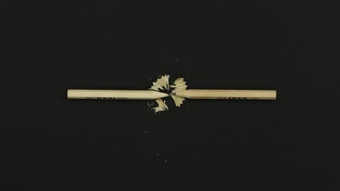 Stop motion animation of moving little wooden pencils on the table with black background. Pencils stitching.