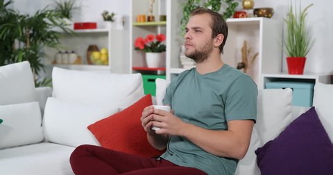 Young Man Having a Tooth Pain While Drinking Hot Tea Sitting on Sofa Living Room