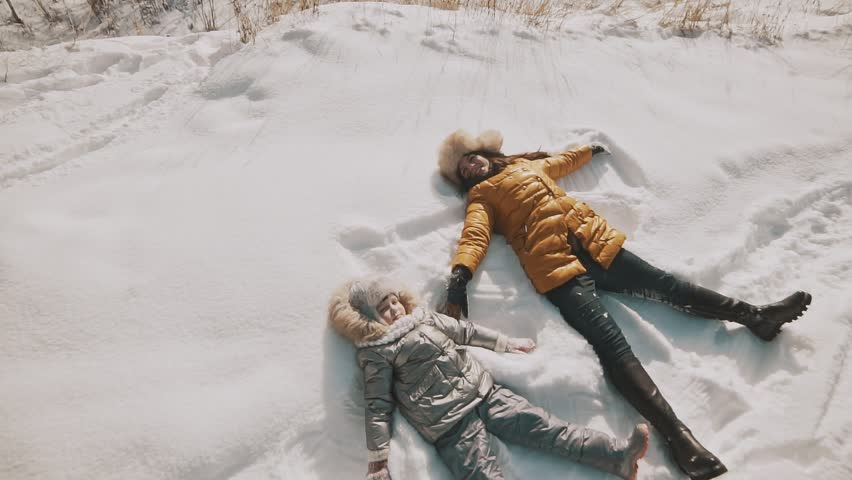 Young mother and little daughter making angels on the snow. Top view with copyspace. Family have fun in sunny winter day outdoors | Shutterstock HD Video #1008221476